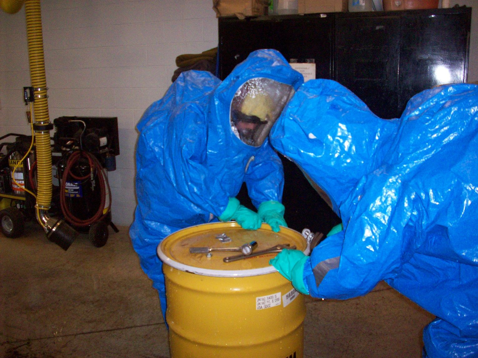 Men in Blue Hazmat Suits Sealing Barrel